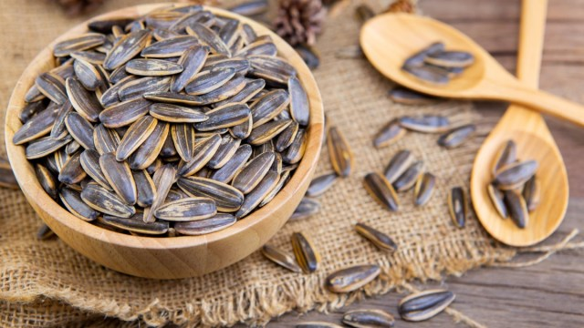 wooden bowl of sunflower seeds on piece of burlap next to two wooden spoons